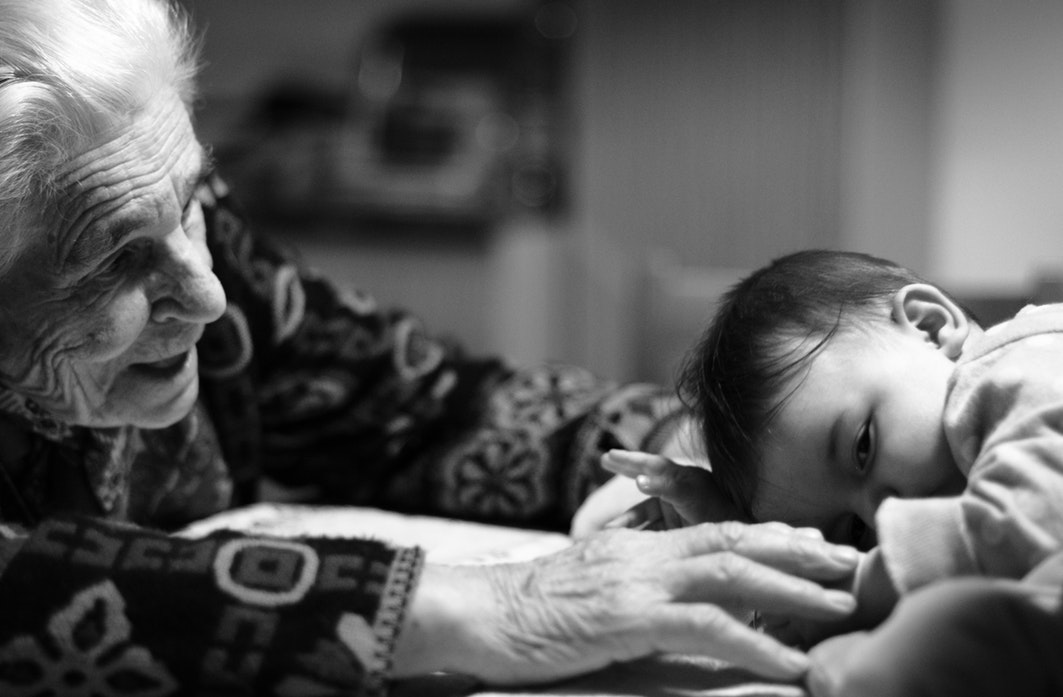 A black and white photo of a grandmother and a baby.
