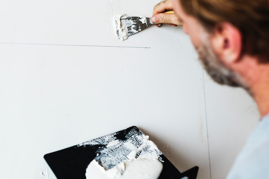 Person repairing a hole in a wall.