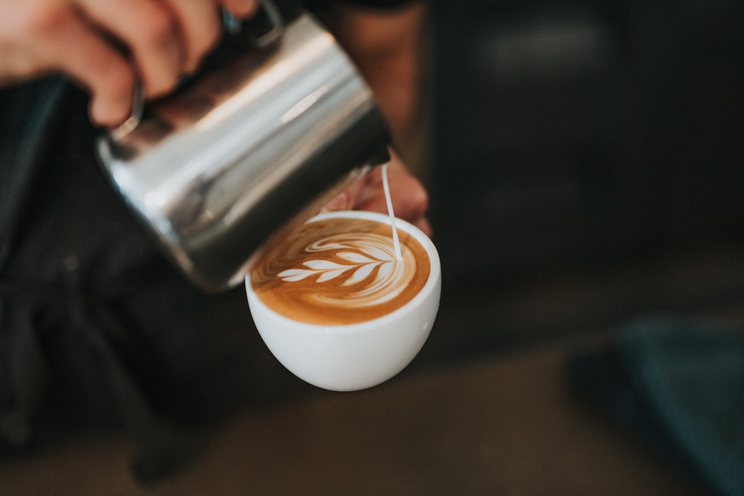 Milk being poured into a latte.